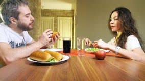 Καυκάσιοι άνδρας και γυναίκα που τρώνε τα χοτ ντογκ και το μαρούλι στο σπίτι απόθεμα βίντεο