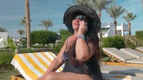 Καυκάσιοι ανώτεροι θηλυκοί ηλικιωμένοι στο μαύρο καπέλο που μιλά σε ένα smartphone και που κάνει ηλιοθεραπεία στον ήλιο να καθίσε απόθεμα βίντεο