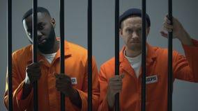 Καυκάσιοι και αφροαμερικανοί φυλακισμένοι που κρατούν τους φραγμούς φυλακών και που κοιτάζουν στη κάμερα απόθεμα βίντεο