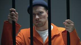 Καυκάσιος άνδρας φυλακισμένος με το σημάδι στους φραγμούς και το κοίταγμα εκμετάλλευσης προσώπου άμεσα φιλμ μικρού μήκους
