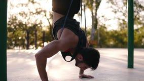 Καυκάσιος αρσενικός αθλητής που κάνει την ώθηση UPS στεμένος στο κεφάλι του με την ασφάλεια ζωνών Κατάρτιση στο τοπικό sportyard απόθεμα βίντεο