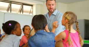 Καυκάσιος αρσενικός δάσκαλος που διδάσκει τα παιδιά του για τη σφαίρα στην τάξη 4k απόθεμα βίντεο