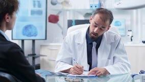Καυκάσιος γιατρός στο σύγχρονο γραφείο με τον ερευνητικό εξοπλισμό που παίρνει τις σημειώσεις από έναν υποψήφιο δοκιμής φαρμάκων απόθεμα βίντεο