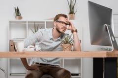 Καυκάσιος επιχειρηματίας που εξετάζει το όργανο ελέγχου υπολογιστών καθμένος στο χώρο εργασίας Στοκ φωτογραφίες με δικαίωμα ελεύθερης χρήσης