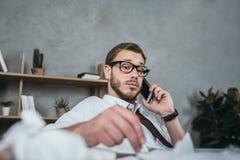Καυκάσιος επιχειρηματίας που μιλά στο smartphone καθμένος στον εργασιακό χώρο Στοκ Φωτογραφία
