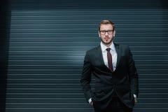 Καυκάσιος επιχειρηματίας που φορά το κοστούμι και eyeglasses, που στέκεται και που εξετάζει τη κάμερα Στοκ φωτογραφίες με δικαίωμα ελεύθερης χρήσης