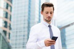 Καυκάσιος επιχειρηματίας που χρησιμοποιεί το smartphone σε υπαίθριο Στοκ φωτογραφία με δικαίωμα ελεύθερης χρήσης