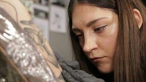 Καυκάσιος θηλυκός καλλιτέχνης δερματοστιξιών στο στάδιο της εργασίας, άποψη κινηματογραφήσεων σε πρώτο πλάνο για το πρόσωπο φιλμ μικρού μήκους