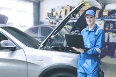 Καυκάσιος μηχανικός που ελέγχει τη μηχανή αυτοκινήτων που χρησιμοποιεί το lap-top υπολογιστών στο κατάστημα επισκευής Στοκ Φωτογραφίες