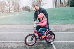 Καυκάσιος μπαμπάς πατέρων που εκπαιδεύει βοηθώντας την κόρη κοριτσιών για να οδηγήσει το ποδήλατο στοκ εικόνα με δικαίωμα ελεύθερης χρήσης