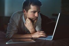 Καυκάσιος νεαρός άνδρας που βρίσκεται στο κρεβάτι στο lap-top του βασική εργασία Στοκ φωτογραφία με δικαίωμα ελεύθερης χρήσης