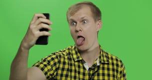 Καυκάσιος νεαρός άνδρας στο κίτρινο πουκάμισο που παίρνει τα συμπαθητικά selfies στο smartphone φιλμ μικρού μήκους