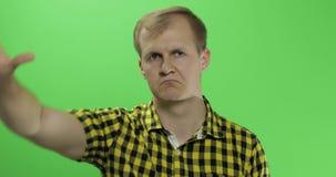 Καυκάσιος νεαρός άνδρας στο κίτρινο πουκάμισο που παρουσιάζει αριθ. και που δίνει τον αντίχειρά του κάτω απόθεμα βίντεο