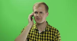 Καυκάσιος νεαρός άνδρας στο κίτρινο πουκάμισο που χρησιμοποιεί το κινητό τηλέφωνο για την κλήση φιλμ μικρού μήκους