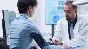 Καυκάσιος παθολόγος που μετρά το presure αίματος με ένα ψηφιακό sphygmomanometer απόθεμα βίντεο