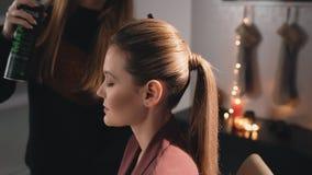 Καυκάσιος πρότυπος ξανθός καλλιτεχνών σύνθεσης κομμωτών hairstyle Διασκορπίζει το βερνίκι και καθιστά την τρίχα τακτοποιημένη Χρη απόθεμα βίντεο