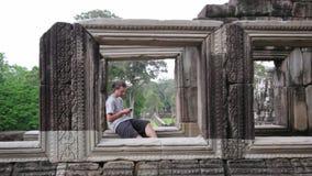 καυκάσιος τουρίστας που χρησιμοποιεί το κινητό τηλέφωνο στο angkor απόθεμα βίντεο