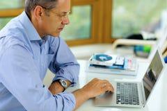 Καυκάσιο άτομο που εργάζεται στο φορητό προσωπικό υπολογιστή του Στοκ Εικόνες