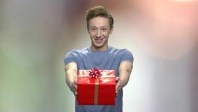 Καυκάσιο αγόρι εφήβων που δίνει το κιβώτιο δώρων απόθεμα βίντεο