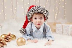 Καυκάσιο αγόρι που φορά τα Χριστούγεννα εορτασμού καπέλων Άγιου Βασίλη ή το νέο έτος Στοκ Εικόνες