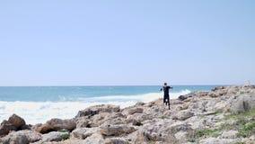 Καυκάσιο αθλητικό άτομο που τρέχει πέρα από τους βράχους σε μια δύσκολη παραλία που φορά τη μαύρη εξάρτηση o απόθεμα βίντεο