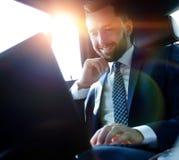 Καυκάσιο αρσενικό ανώτατο στέλεχος επιχείρησης που ταξιδεύει με ένα αυτοκίνητο και που εργάζεται στο φορητό προσωπικό υπολογιστή στοκ εικόνα με δικαίωμα ελεύθερης χρήσης