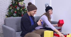 Καυκάσιο ζεύγος που στρεβλώνει ένα δώρο φιλμ μικρού μήκους