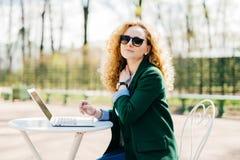 Καυκάσιο θηλυκό freelancer με τη χνουδωτή ξανθή τρίχα που φορά τα καθιερώνοντα τη μόδα ενδύματα και τα γυαλιά ηλίου που λειτουργο στοκ φωτογραφίες