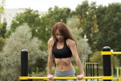 Καυκάσιο κορίτσι brunette που κλίνεται στους αθλητικούς φραγμούς Η προκλητική νέα γυναίκα ικανότητας σε υπαίθριο επιλύει τη γυμνα Στοκ Εικόνες