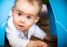 Καυκάσιο κοριτσάκι που συμπιέζει στο πλαίσιο του πλαστικού πίνακα παιχνιδιών στοκ εικόνες με δικαίωμα ελεύθερης χρήσης