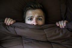 Καυκάσιο κρύψιμο νεαρών άνδρων στο κρεβάτι κάτω από το κάλυμμα στο σπίτι στοκ εικόνες