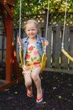 Καυκάσιο μικρό παιδί κοριτσιών στην ταλάντευση στην παιδική χαρά κατωφλιών έξω στοκ φωτογραφία με δικαίωμα ελεύθερης χρήσης