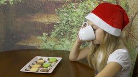 Καυκάσιο νέο κορίτσι στην κόκκινη συνεδρίαση καπέλων στον πίνακα στην εγχώρια κουζίνα Το κορίτσι πίνει το άσπρο φλυτζάνι νερού ή  απόθεμα βίντεο