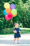 Καυκάσιο παιδί κοριτσιών στο μπλε φόρεμα με τα ζωηρόχρωμα μπαλόνια, στο πάρκο λιβαδιών τομέων στοκ εικόνα