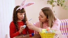 Καυκάσιο χρώμα εμφάνισης μητέρων και κορών αντί ενός αυγού Πάσχας, κορίτσι με ένα μεγάλο χαμόγελο φιλά το mom του απόθεμα βίντεο