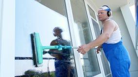 Καυκάσιο όμορφο άτομο, εργαζόμενος της καθαρίζοντας υπηρεσίας, στις μπλε φόρμες, με τα ακουστικά, καθαρισμός, πλένοντας παράθυρα  απόθεμα βίντεο