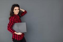 Καυκάσιο lap-top εκμετάλλευσης κοριτσιών σπουδαστών χαμόγελου πέρα από το γκρίζο υπόβαθρο Στοκ φωτογραφία με δικαίωμα ελεύθερης χρήσης