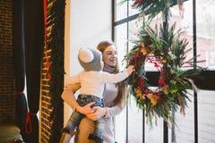 Καυκάσιο mom διακοπών έτους και Χριστουγέννων θέματος το νέο κρατά το γιο στα όπλα της για 1 έτος στο σπίτι σε ένα εσωτερικό σοφι στοκ εικόνες