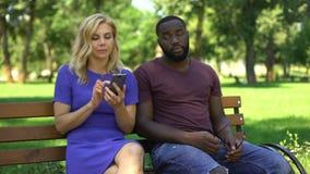 Καυκάσιο smartphone παιχνιδιού γυναικών κατά την ημερομηνία στο πάρκο, που αγνοεί τον ανησυχημένο φίλο απόθεμα βίντεο