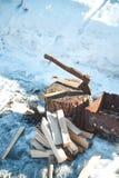 Καυσόξυλο και τσεκούρι κοντά στη σχάρα οι διακοπές αγοριών βάζουν το χειμώνα χιονιού Στοκ εικόνα με δικαίωμα ελεύθερης χρήσης