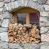 Καυσόξυλο logpile που συσσωρεύει σε ένα παράθυρο Στοκ Φωτογραφία