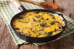 Καυτά ανακατωμένα αυγά με το σπανάκι, το τυρί τυριού Cheddar και τα μανιτάρια μέσα Στοκ Φωτογραφία