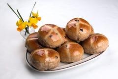 Καυτά διαγώνια κουλούρια που συσσωρεύονται σε ένα ωοειδές πιάτο με τα daffodils Στοκ φωτογραφίες με δικαίωμα ελεύθερης χρήσης