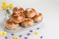 Καυτά διαγώνια κουλούρια σε ένα ωοειδές πιάτο, με ένα βάζο των λουλουδιών Στοκ φωτογραφίες με δικαίωμα ελεύθερης χρήσης