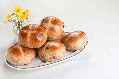 Καυτά διαγώνια κουλούρια σε ένα ωοειδές πιάτο με τα λουλούδια άνοιξη Στοκ Φωτογραφίες