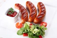 Καυτά και τηγανισμένα λουκάνικα με τα λαχανικά και τα καρυκεύματα Στοκ Εικόνες
