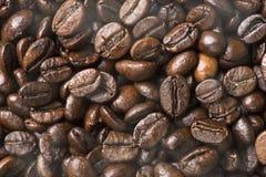 Καυτά μαύρα ψημένα arabica φασόλια καφέ με την επίδραση καπνού Στοκ Φωτογραφία