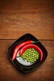 Καυτά πιπέρια τσίλι και πράσινα τριζάτα πρόχειρα φαγητά μπιζελιών στο κεραμικό πιάτο Στοκ φωτογραφίες με δικαίωμα ελεύθερης χρήσης