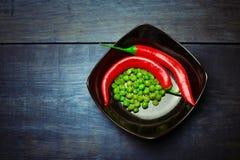 Καυτά πιπέρια τσίλι και πράσινα τριζάτα πρόχειρα φαγητά μπιζελιών στο κεραμικό πιάτο Στοκ φωτογραφία με δικαίωμα ελεύθερης χρήσης