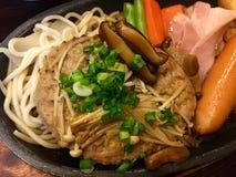 Καυτά χάμπουργκερ χοιρινού κρέατος και τηγάνι λουκάνικων Στοκ Εικόνα